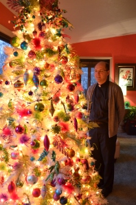 The Rev. William Debo stands near one of the 31 full-sized trees in the rectory.